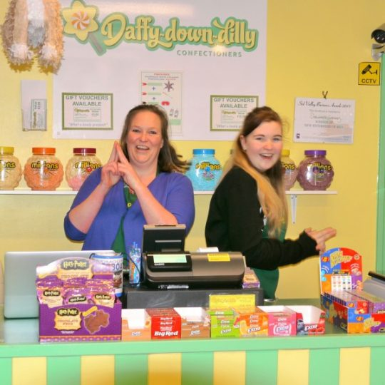 Staff photo inside Daffy-down-dilly showing a selection of American chewing gums and featuring Natalie Brittain and Lucy Coles