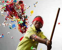a blindfolded child having a great time trying to break open Piñatas that has been filled with sweets