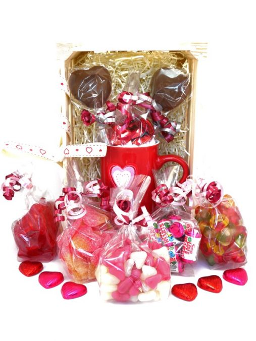 an image of one of our sweet Valentines hampers, containing a mug, hot chocolates, and jelly and fizzy sweets with a heart theme