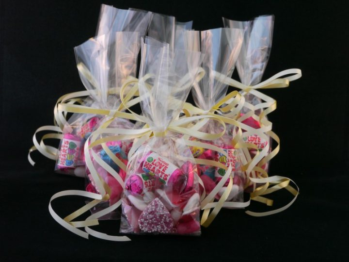 A group photo of several wedding favour bags tied with gold ribbons and filled with love heart sweets, jelly heart sweet and chocolate heart sweets