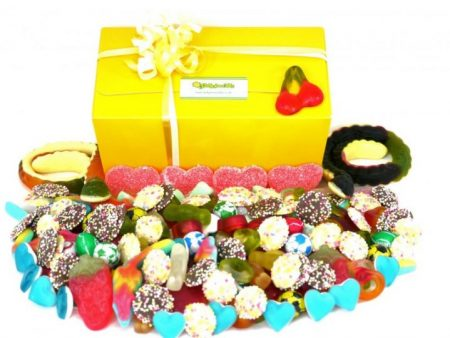 In front of our yellow presentation sweet box, a image of 1 kilo of assorted sweets. the perfect gift for anyone with a sweet tooth, chocolates, jelly sweets and fizzy sweets all nestle together in this stunning, colourful and delicious display.