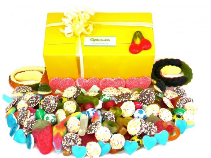 Pick and Mix sweet box. In front of our yellow presentation sweet box, a image of 1 kilo of assorted sweets. the perfect gift for anyone with a sweet tooth, chocolates, jelly sweets and fizzy sweets all nestle together in this stunning, colourful and delicious display.