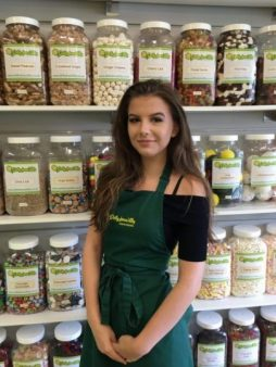 Image of one of of our sweet shop staff, Sophie Raw standing in front of some of our 350 jars of sweets