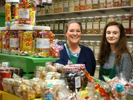 Sweet shop staff smiling and welcoming customers. Featuring Emma Tompkins and Natalie Brittain